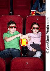 Niños compartiendo palomitas en el cine 3D