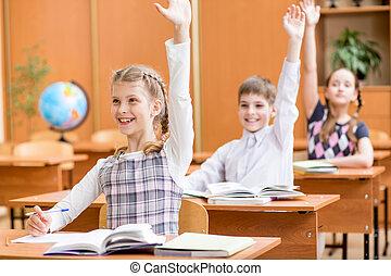 Niños de escuela con las manos levantadas en clase