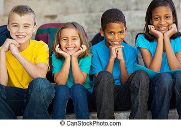 Niños de escuela primaria sentados al aire libre
