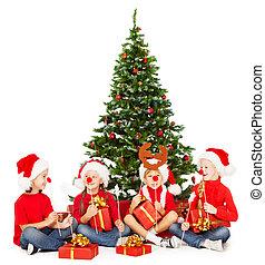 Niños de Navidad con sombrero rojo jugando bajo el árbol. Nuevos regalos y accesorios