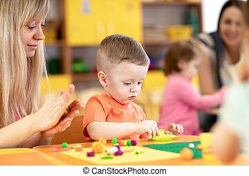 Niños en clase en la guardería. Bebé bebé jugando con plastilina con profesor en la sala de juegos de niños.