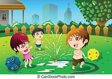 Niños jugando con agua de aspersor en verano