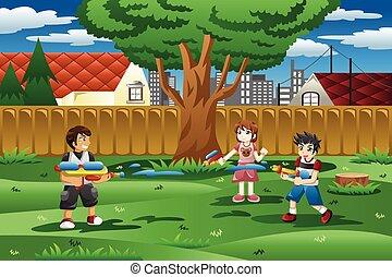 Niños jugando con pistola de agua en el patio trasero