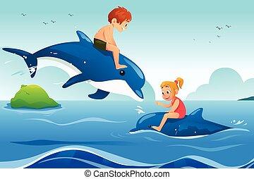 Niños pequeños nadando con delfines en el océano