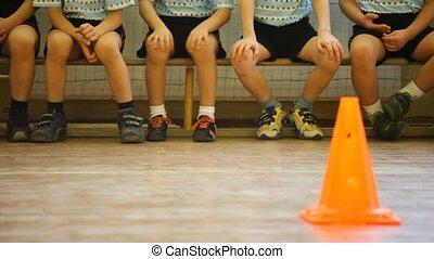 Niños sentados en el banquillo en el salón de deportes
