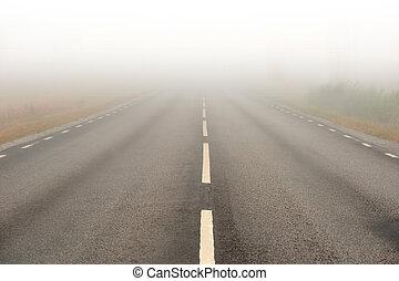 niebla pesada, camino de asfalto