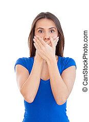 No más palabras. Una joven sorprendida cubriendo la boca con las manos mientras está aislada en blanco
