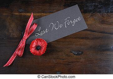 No olvidemos, insignias rojas de hojalata para el 11 de noviembre, la apelación del día del recuerdo, en el fondo de madera reciclado oscuro.