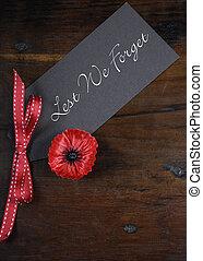 No olvidemos, insignias rojas de hojalata para el 11 de noviembre, la apelación del día del recuerdo, en el fondo de madera reciclado oscuro. Vertical.