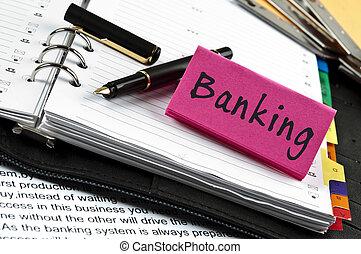 Nota bancaria en agenda y pluma