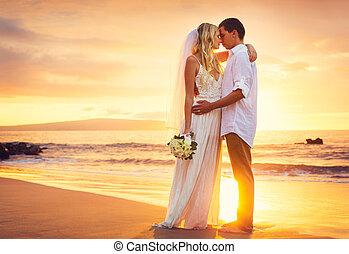 Novia y novio, besándose al atardecer en una hermosa playa tropical, romántica pareja casada