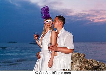 Novia y novio en una playa tropical bebiendo vino de copas w
