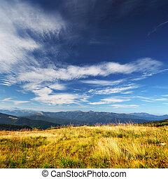 Nubes sobre montañas y gras amarillos
