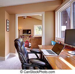 Oficina y computadora y silla con paredes marrones.