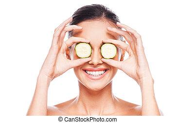 Ojos sanos. Hermosa joven mujer sin camisa sosteniendo rodajas de pepino frente a sus ojos mientras se enfrenta a fondo blanco