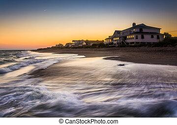 Olas en el Océano Atlántico y casas frente a la playa al atardecer, Edis