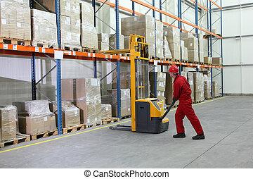 Operador de carretilla elevadora manual en el trabajo en el almacén