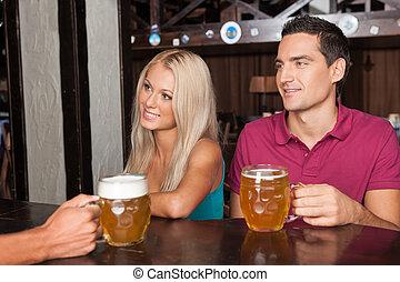 Ordenando cerveza. Una hermosa pareja joven pidiendo cerveza en el bar