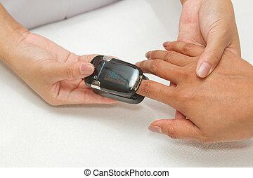 Paciente con oximetro de pulso en el dedo para monitorear