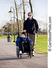 Padre caminando con el hijo discapacitado en silla de ruedas