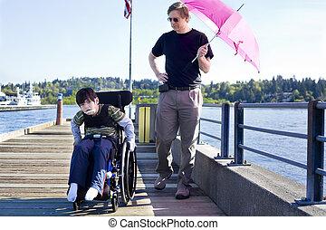 Padre caminando con su hijo discapacitado en el muelle del lago