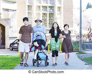 Padre caminando con sus hijos birraciales al aire libre. Un hijo discapacitado en silla de ruedas tiene parálisis cerebral.