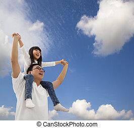 Padre y hija asiáticos bajo el campo de nubes