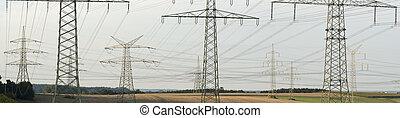 Panorama de muchos pilones eléctricos para el suministro de energía