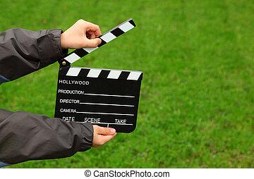 Pantalla de cine en manos de chico con chaqueta en el campo con hierba verde