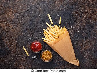 Papas fritas en una bolsa de papel con salsas