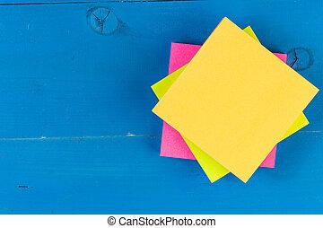 Papel de bloque vacío para el texto. Copia espacio en el papel amarillo sobre tablas de fondo de madera azul.