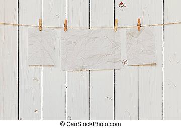 Papel viejo en blanco colgando de madera blanca con espacio para texto.