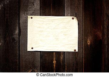 Papel viejo pegado a una pared de madera