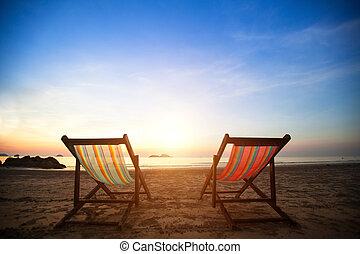Par de playeros de playa en el mar de la costa desierta al amanecer, perfecto concepto de vacaciones.