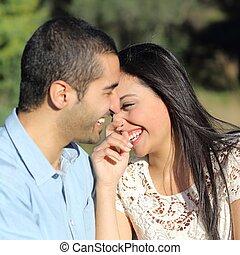 Pareja casual árabe flirteando riéndose feliz en un parque