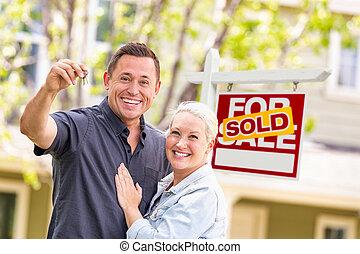 Pareja caucásica frente a la venta de inmobiliaria y casa con llaves
