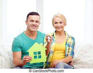 Pareja con casa verde y llaves en casa nueva