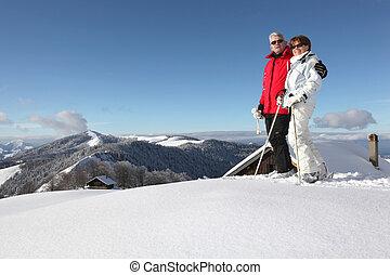 Pareja de mediana edad esquiando