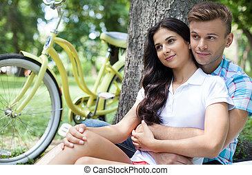 Pareja en el parque. Alegre pareja de jóvenes sentados juntos y apoyados en el árbol