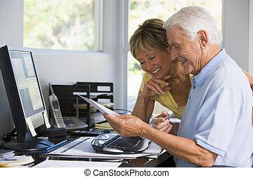 Pareja en la oficina central con ordenador y papeleo sonriendo
