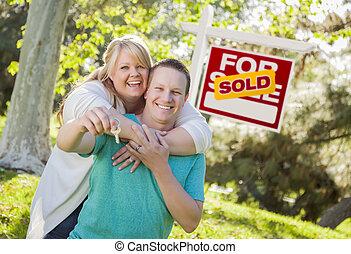Pareja frente a un letrero de bienes raíces con llaves