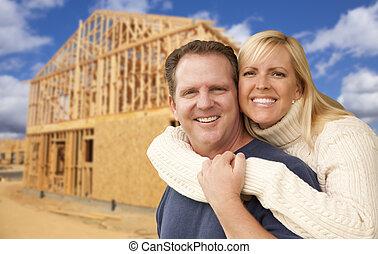 Pareja frente a una nueva casa de construcción