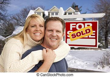 Pareja frente a una nueva casa y un letrero de bienes raíces