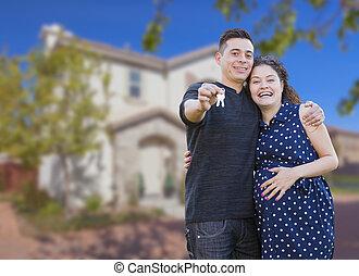 Pareja hispana con llaves de casa en frente de un nuevo hogar