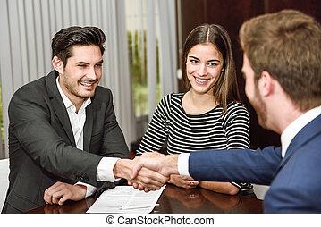 pareja, joven, agente, manos, sonriente, sacudida, seguro