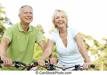 Pareja madura montando bicicletas