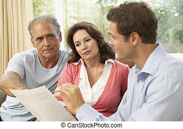 Pareja mayor con asesor financiero en casa