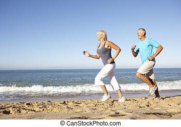 Pareja mayor con ropa de gimnasia corriendo por la playa