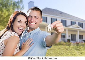Pareja militar con llaves de casa en frente de un nuevo hogar