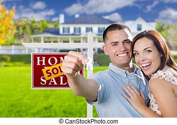 Pareja militar frente a casa, llaves de casa y firma